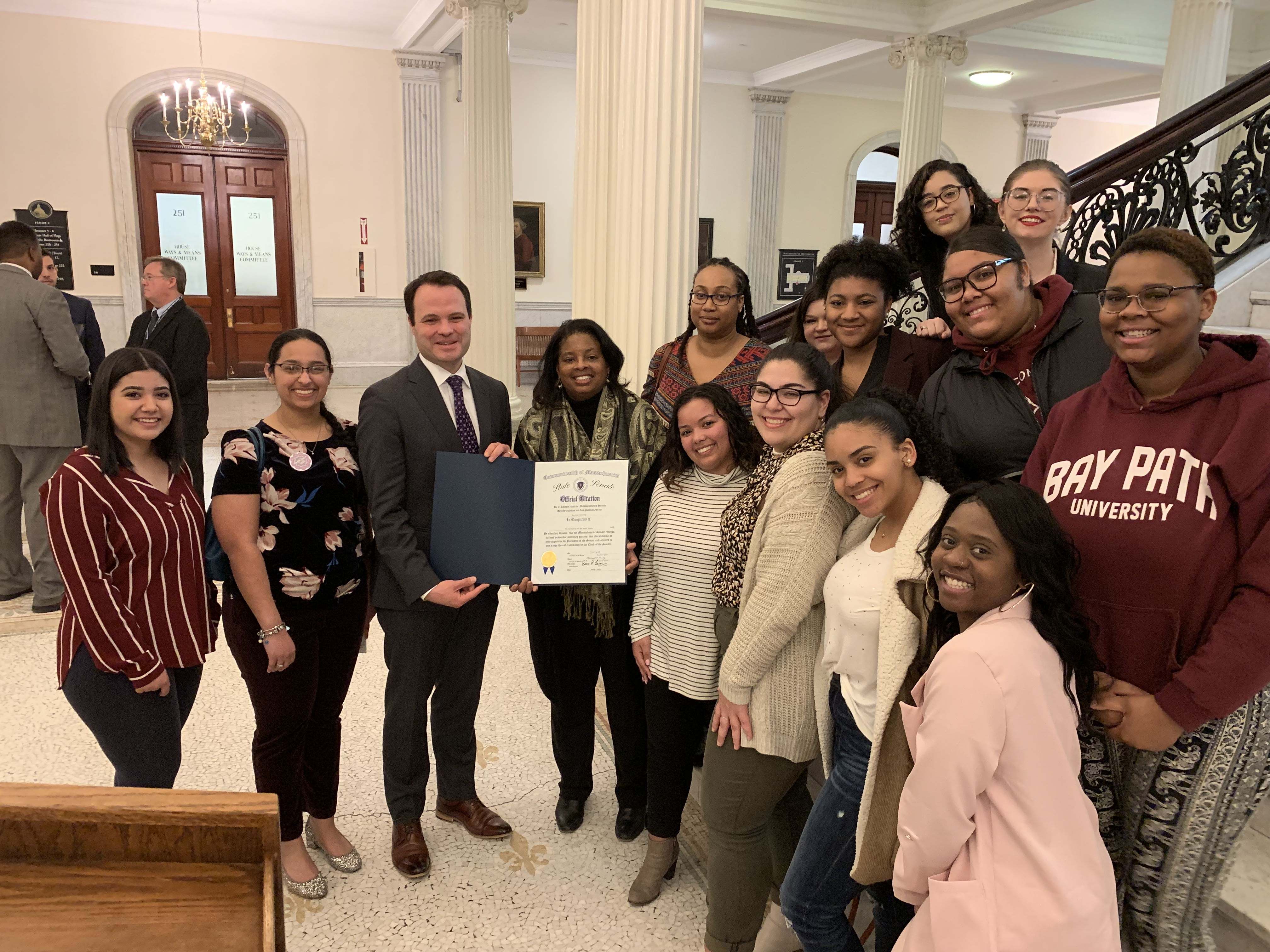Senator Lesser presenting the proclamation to Bay Path students