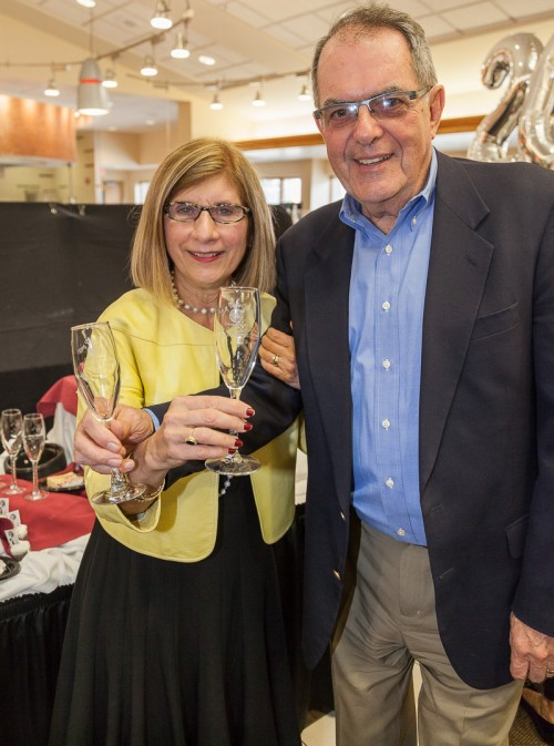 Photo of Dr. Carol and Noel Leary celebrating with champagne glasses