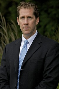 man looking at camera with short brown hair, wearing a white shirt, blue tie and business suit
