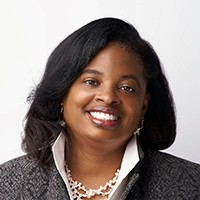 Professor Janine Fondon smiling at camera wearing a white shirt with black patterned jacket.