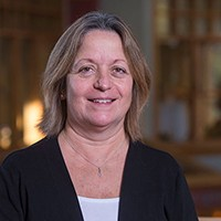 Professor Foley is a women with short brown hair, wearing a white shirt with a black jacket. She is smiling at the camera.
