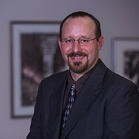 Professor Mennella is smiling at the camera. He is wearing a dark colored suit and has glasses.